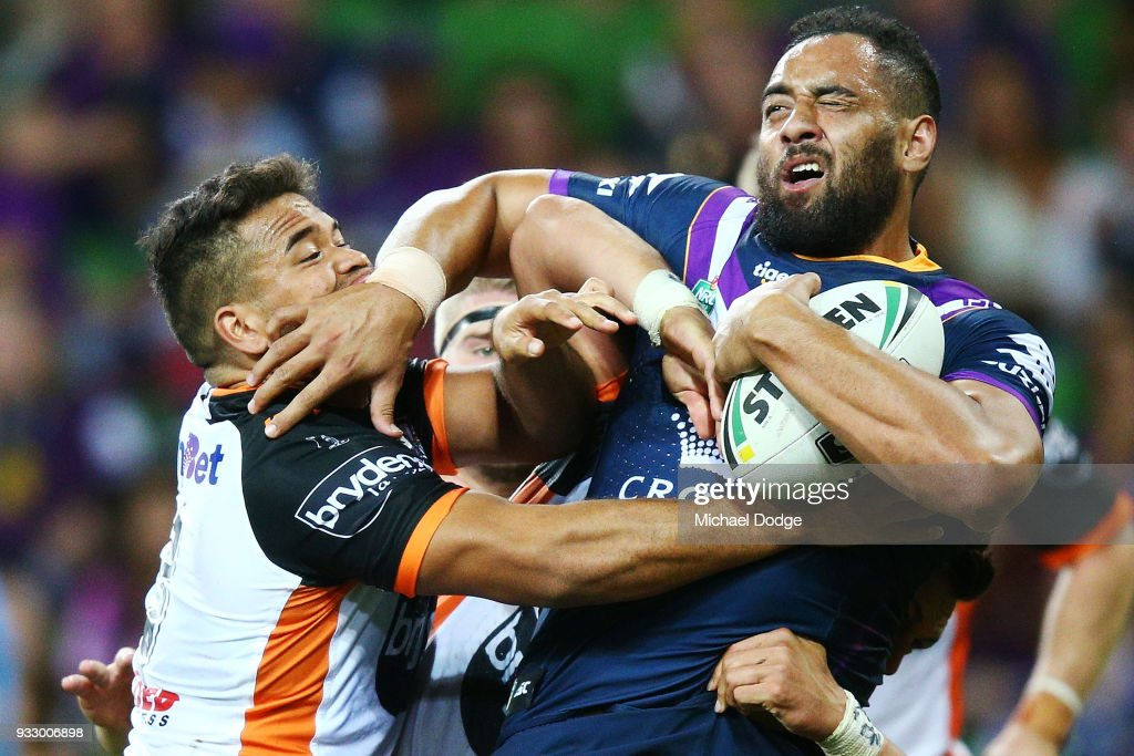 Esan Marsters of the Tigers tackles Sam Kasiano of the Storm during the round two NRL match between the Melbourne Storm and the Wests Tigers at AAMI Park on March 17, 2018 in Melbourne, Australia.