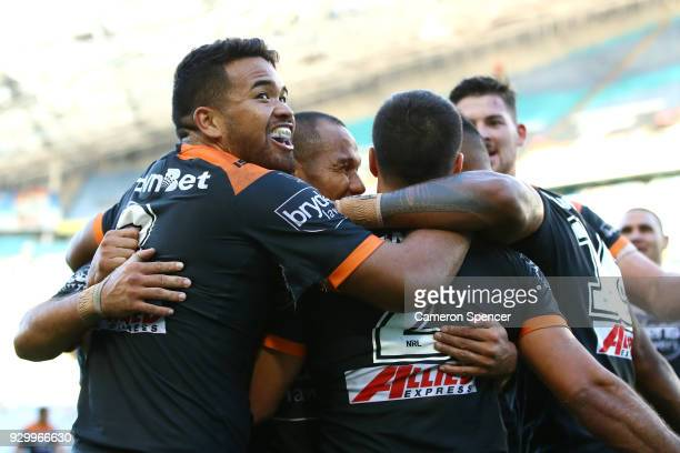 Esan Nike Marsters of the Tigers and team mates congratulate team mate Corey Thompson of the Tigers after scoring a try during the round one NRL...