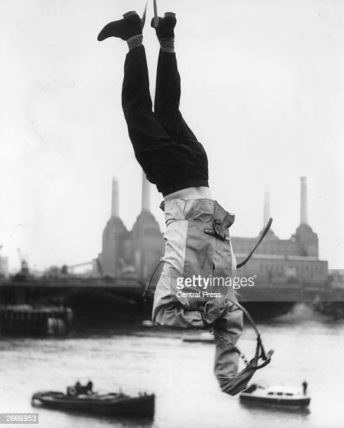 Escapology adviser Timothy DillRussell hanging upside down over the Thames while trying to escape from a straight jacket a trick performed by Houdini...