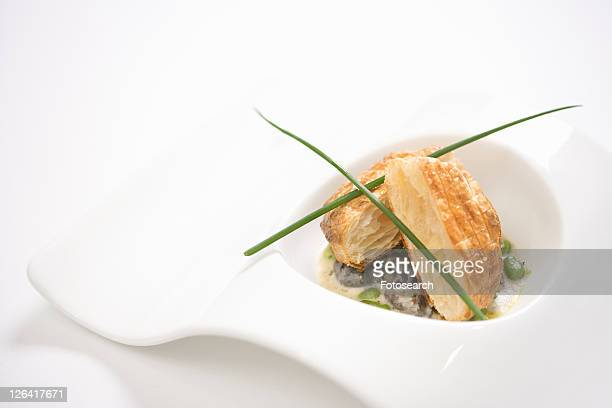 Escargot en croute with butter and fava beans.