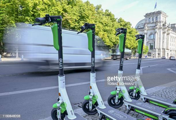 Escooter for rent are parked near the Reichstag building as a delivery truck drives past them in Berlin on June 19 2019 Germany had authorised on...