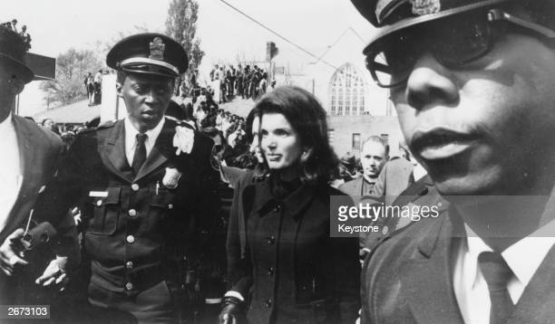 Escorted by a policeman Jacqueline Kennedy widow of the assassinated US President arrives at the funeral service for Dr Martin Luther King Jr at the...