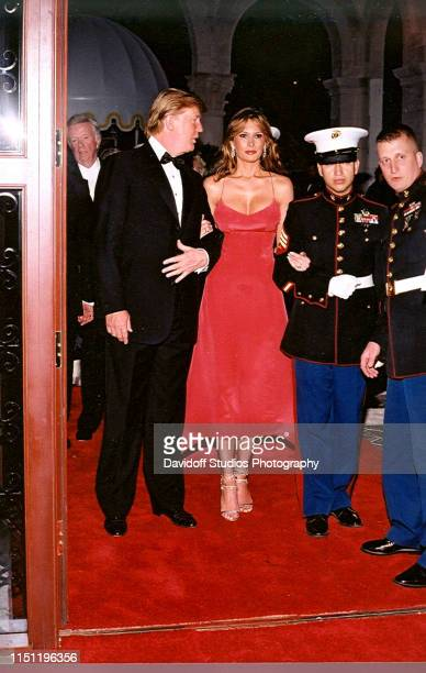 Escorted by a US Marine color guard married couple American real estate developer Donald Trump and model Melania Trump arrive at the Red Cross Ball...