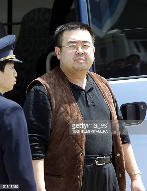Escorted by an immigration officer a man believed to be Kim JongNam son of North Korean leader Kim JongIl gets off a bus to board an ANA905 airplane...