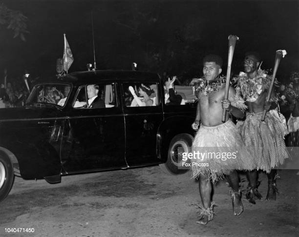 Escorted by Fijian torchbearers Queen Elizabeth II and Prince Philip are driven to the Grand Pacific Hotel in Suva where a ball is being held in...