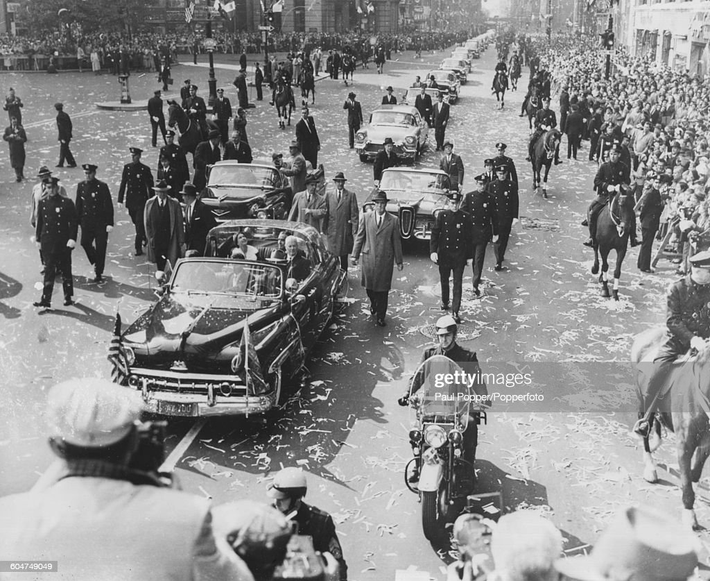 Escorted by policemen on foot, horseback and on motorcycles, Queen Elizabeth II (in the back seat, looking up) rides in a bubble top Lincoln limousine car as part of a royal motorcade with New York Governor Averell Harriman (centre) and official greeter Richard C Patterson Jnr (right), as they drive past crowds of people near City Hall after arriving in New York, October 22nd 1957.