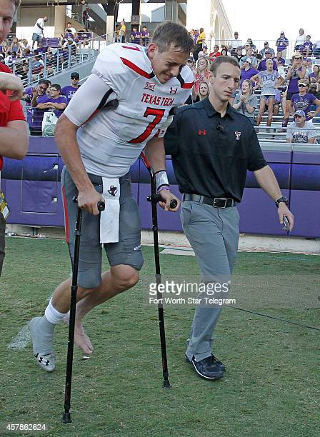 Escorted by trainers and on crutches in the third quarter Texas Tech quarterback Davis Webb grimaces as he leaves the game against Texas Christian...