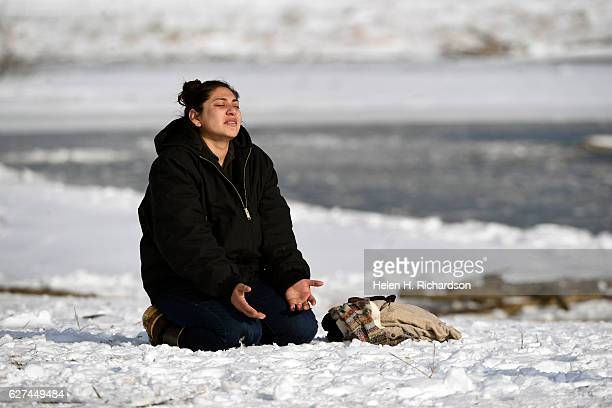 Esdee of the Tachi nation prays near the Cannon Ball river at Oceti Sakowin Camp on the edge of the Standing Rock Sioux Reservation on December 3,...