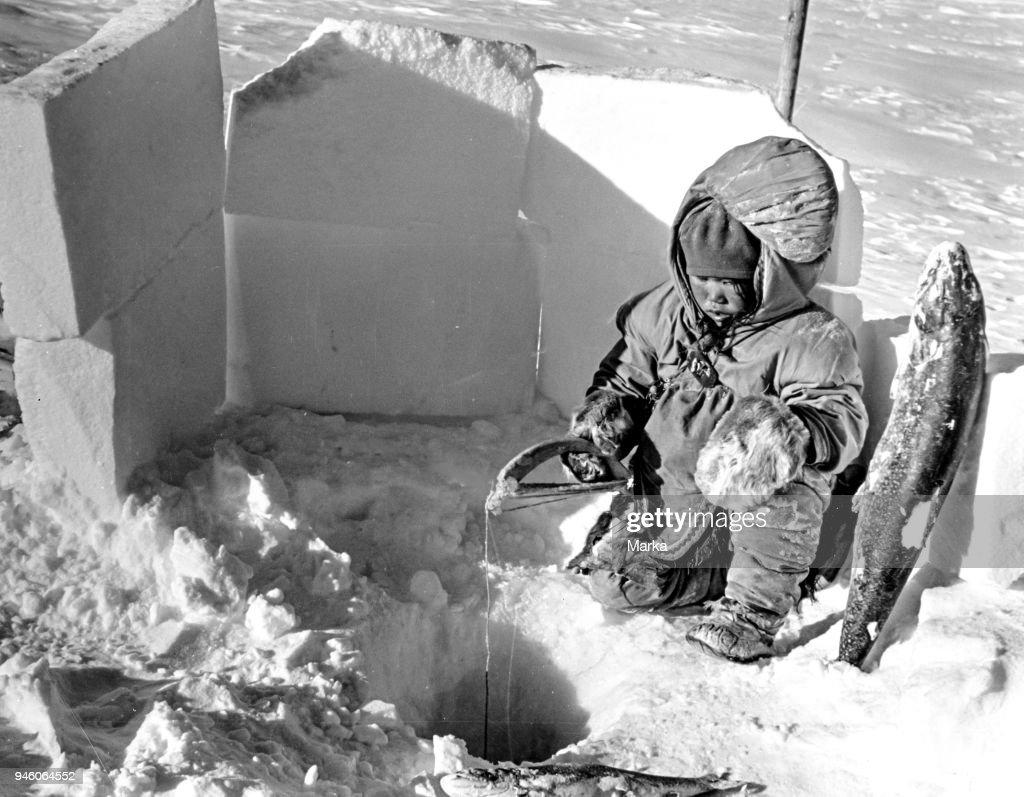 Eskimo Child Fishing In The Igloo : News Photo
