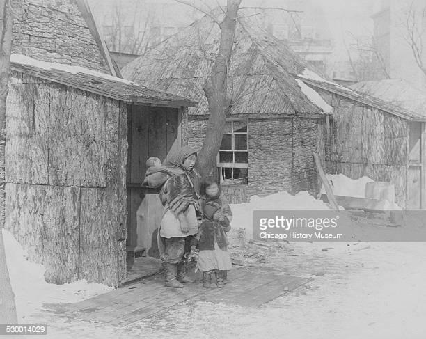 Eskimos standing near a structure in the Eskimo village at the World's Columbian Exposition Chicago Illinois 1893