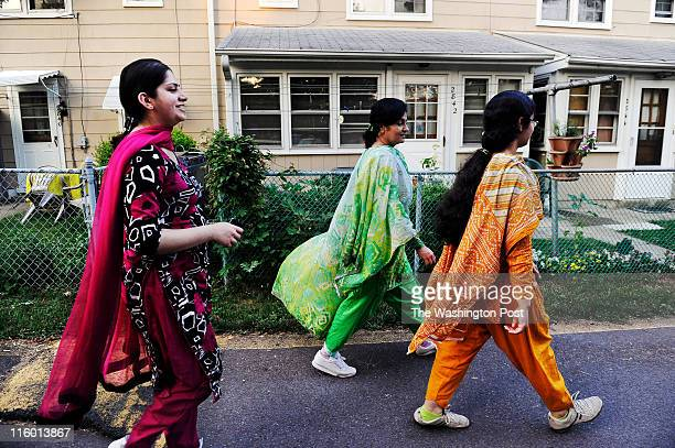 Esma Waqar left and her sister Muzma Sheikh middle and neice Alja Sheikh get their daily exercise by walking laps around the Hillwood Square...