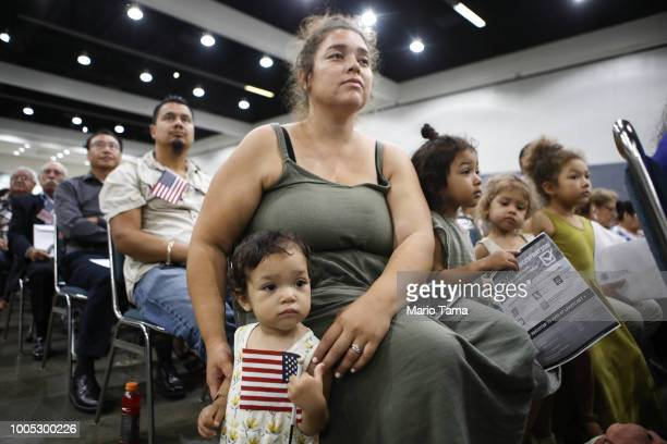 Esme Gomez already a citizen is held by her mother Belinda before her father from El Salvador is sworn in as a US citizen at a naturalization...