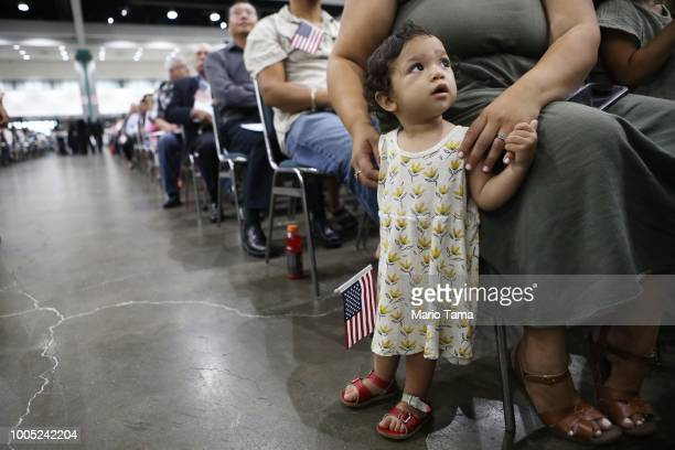 Esme Gomez already a citizen waits before her father from El Salvador is sworn in as a US citizen at a naturalization ceremony on July 25 2018 in Los...