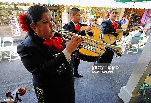 Esmeralda Garcia Guillermo Nunez and Mariana Nanez members of the allfemale strolling Mariachi band Ellas Son performs at Los Angeles Farmer Market...