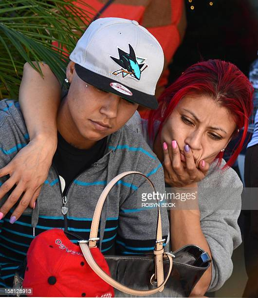 Esmeralda Gonzalez and her friend Karina Vasquez from Van Nuys California grieve at a memorial of flowers candles ballons and notes to the late...