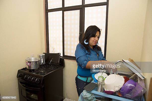 Esmeralda Velazquez a machine operator at an auto suspension plant washes dishes in her home in Queretaro Mexico on Sunday Oct 26 2014 Velazquez...