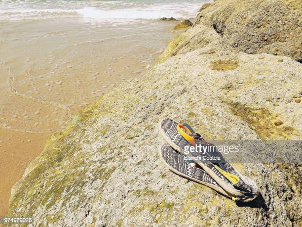 Espadrilles and keys on a rock on the beach in spring
