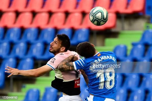 Espanyol's Argentinian forward Jonathan Calleri and Getafe's Uruguayan midfielder Mauro Arambarri jump for the ball during the Spanish league...