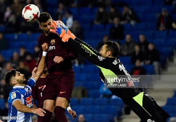 Espanyol's defender Didac Vila and Espanyol's goalkeeper Diego Lopez vie with Barcelona's defender Gerard Pique during the Spanish 'Copa del Rey'...