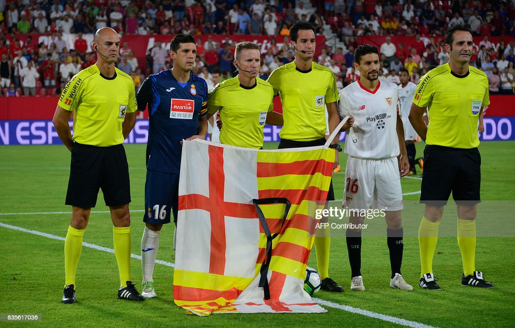 Espanyol's defender Javier Lopez (L), Sevilla's midfielder Jesus Navas (R) and referees pose with the flag of Barcelona and a black ribbon in tribute to the victims of Barcelona attacks before the Spanish league football match Sevilla FC vs Espanyol at the Ramon Sanchez-Pizjuan in Sevilla on August 19, 2017. QUICLER