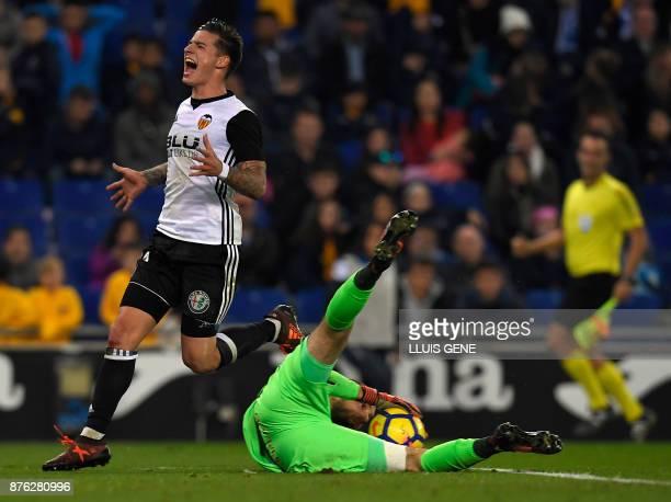 Espanyol's Spanish goalkeeper Pau Lopez gets the ball beside Valencia's Spanish forward Santiago Mina Lorenzo during the Spanish league football...