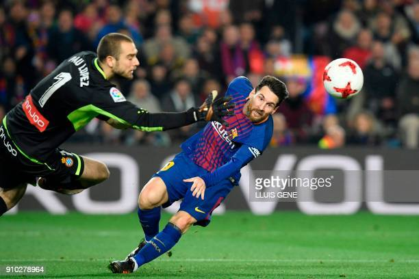 Espanyol's Spanish goalkeeper Pau Lopez tries to block a shot on goal by Barcelona's Argentinian forward Lionel Messi during the Spanish 'Copa del...