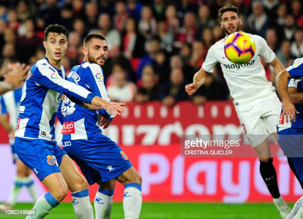 Espanyol's Spanish midfielder David Lopez eyes the ball shot by Sevilla's Argentinian defender Gabriel Mercado to score a goal during the Spanish...