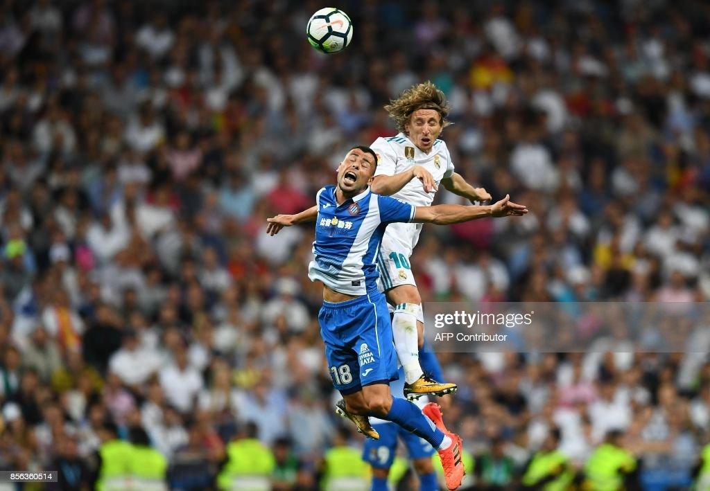 Espanyol's Spanish midfielder Javier Fuego (L) heads the ball with Real Madrid's Croatian midfielder Luka Modric during the Spanish league football match Real Madrid CF vs RCD Espanyol at the Santiago Bernabeu stadium in Madrid on October 1, 2017. /
