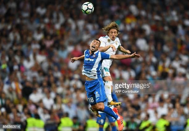 Espanyol's Spanish midfielder Javier Fuego heads the ball with Real Madrid's Croatian midfielder Luka Modric during the Spanish league football match...