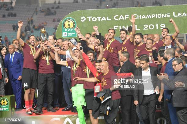 Esperance de Tunis players hold hold up the trophy after winning during the 2nd leg of CAF champion league final 2019 football match between...