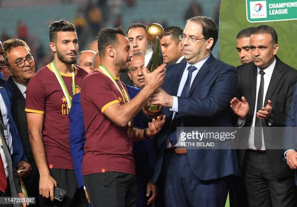 Esperance de Tunis team captain Moez ben Cherifia and Tunisian prime minister Youssef Chahed pose with a trophy after winning during the 2nd leg of...