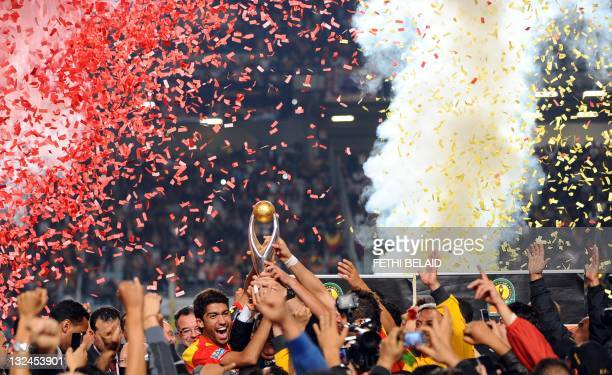 Esperance de Tunis Team captain Oussama Darragi celebrates with the trophy after beating Morocco's WA Casablanca on November 12 2011 during their...