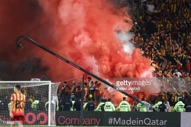 Esperance's fans light up flares as they cheer for their team during the 2019 FIFA Club World Cup quarterfinal football match between Hilal and...