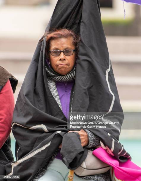Esperanza Barosio of Santa Ana CA wraps her self in a flag to keep warm as she waits for the Annual May Day rally to being at Sasscer Park in Santa...