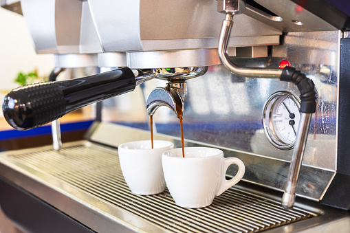 Espresso coffee machine brewing two shots in white cups, professional Italian equipment at restaurant or bar counter, close-up 1134558380
