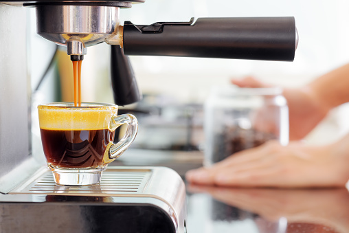 Espresso coffee machine in kitchen. Coffee pouring into cup 590586660