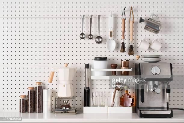 espresso coffee maker and accessories on pegboard - keukengereedschap stockfoto's en -beelden