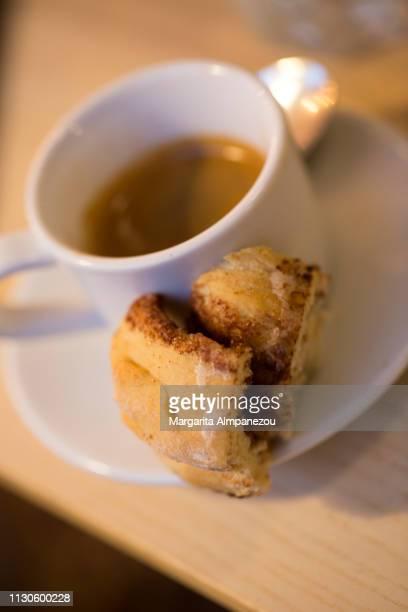 Espresso coffee served with a piece of cinnamon bun