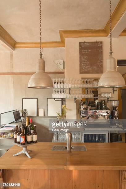 Espresso machine, glasses and bottles behind vintage cafe counter