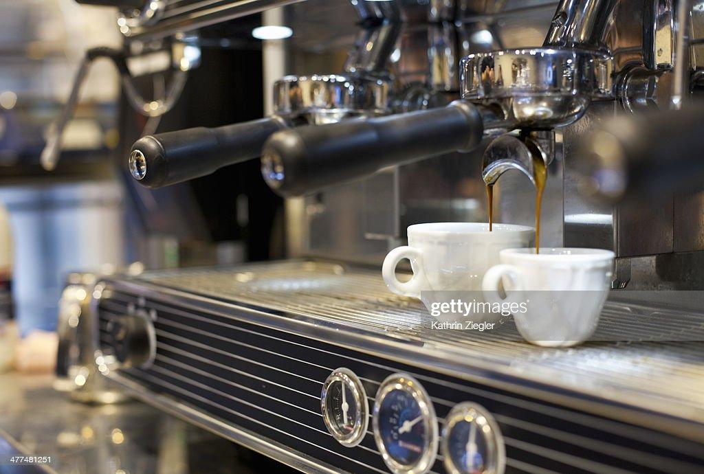 espresso machine pouring coffee into cups : Stock Photo