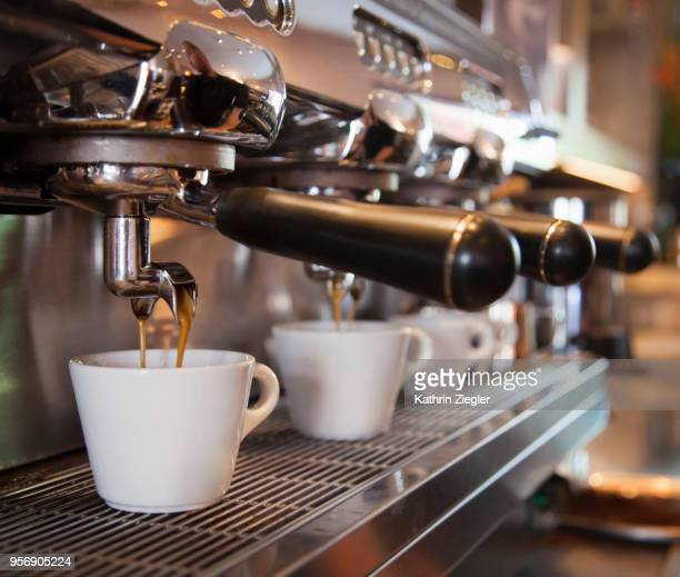 espresso machine pouring coffee into cups - coffee shop stock-fotos und bilder