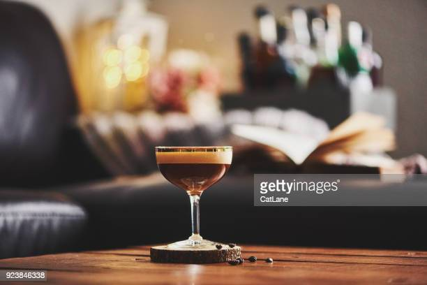 espresso martini cocktail in indoor setting with coffee beans and book on coffee table - espresso stock photos and pictures