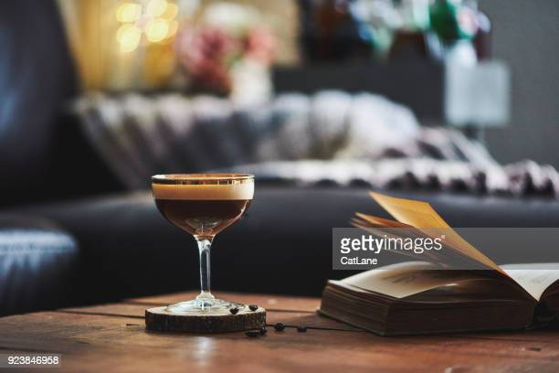 Espresso martini cocktail in indoor setting with coffee beans and book on coffee table