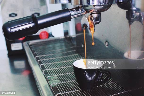 Espresso Pouring In Cup From Coffee Maker At Cafe