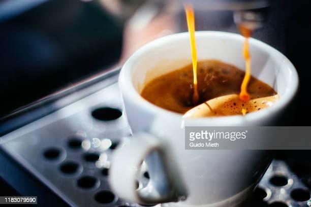 espresso shot pouring out. - fare una pausa foto e immagini stock