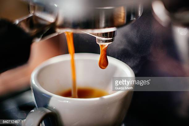 espresso shot pouring out. - espresso stock photos and pictures