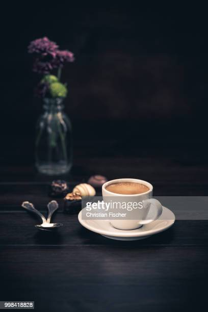 Espresso with chocolate candies on a wooden background