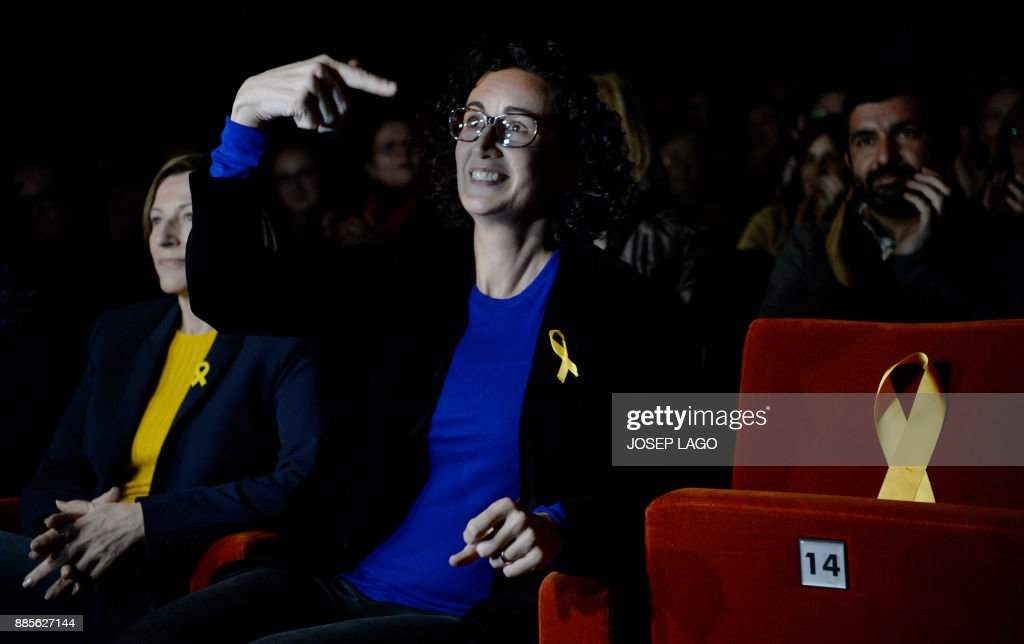 'Esquerra Republicana de Catalunya' - ERC (Republican Left of Catalonia) cadidate for the upcoming Catalan regional election, Marta Rovira (C) points to a seat with a yellow ribbon for the former Catalan vice-president in jail, Oriol Junqueras, during the campaign opening meeting in Vic, on December 4, 2017. Catalans remain deeply split on independence, and several polls suggest pro-secession parties might struggle to win enough seats to form a new regional government after the December 21 regional election. PHOTO / Josep LAGO