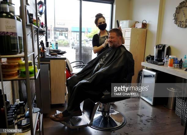 Esra Demir styles the hair of customer Ken Menendez at Salon Loft in Atlanta, Georgia on April 24, 2020. - Governor Brian Kemp has eased restrictions...