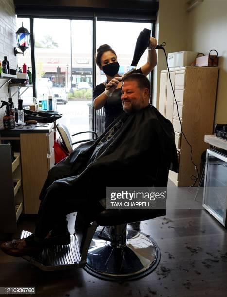 Esra Demir styles the hair of customer Ken Menendez at Salon Loft in Atlanta Georgia on April 24 2020 Governor Brian Kemp has eased restrictions...